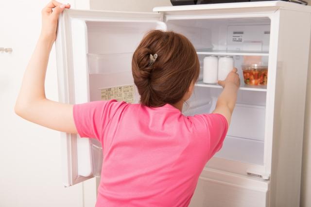 冷蔵庫の中を見ている女性の写真