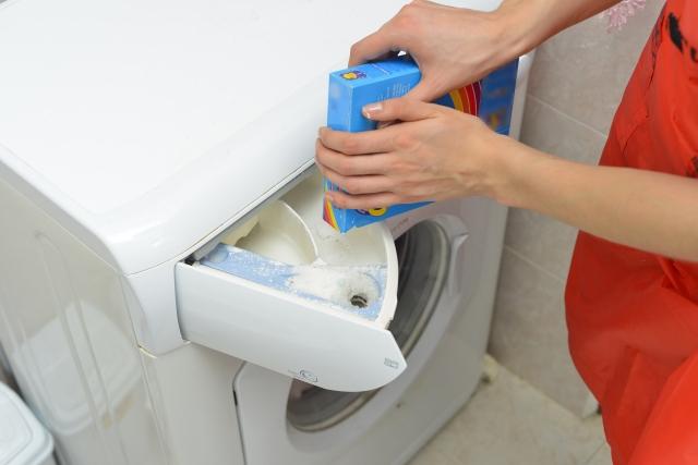 洗濯機に洗剤を入れている写真