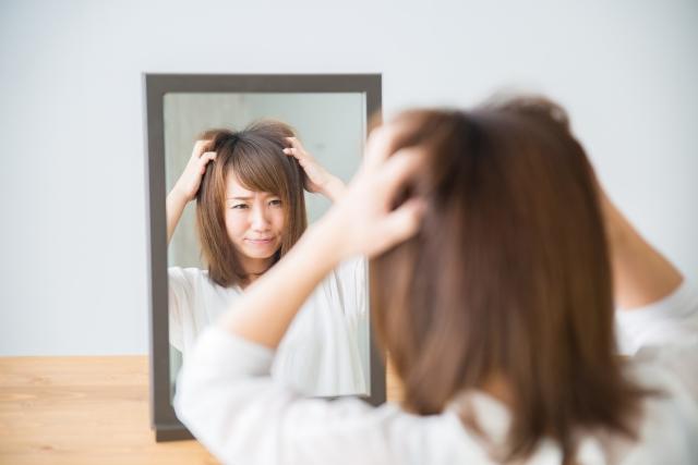 髪の毛で悩んでいる女性