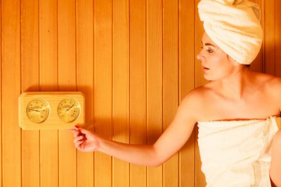 Beauty health spa concept. Woman relaxing in sauna interior looking on equipment thermometer and hygrometer.